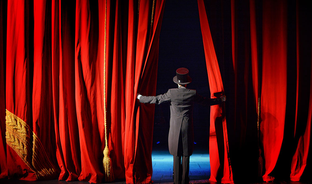 Man opening theatre red curtains